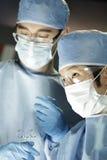 Aziatische chirurg die met medewerker in chirurgie werken royalty-vrije stock afbeeldingen