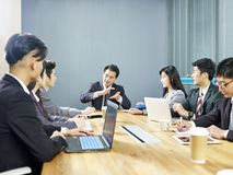 Aziatische collectieve bedrijfsmensen die in bureau samenkomen royalty-vrije stock afbeeldingen