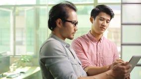 Aziatische collectieve stafmedewerkers die zaken in bureau bespreken