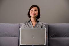 Aziatische dame in bedrijfskledij, die een computer met behulp van stock fotografie