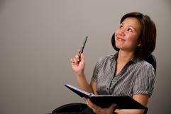 Aziatische dame in bedrijfskledij, die een idee krijgt Stock Foto's