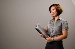 Aziatische dame in bedrijfskledij, die een notitieboekje houdt Stock Afbeelding