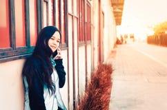 Aziatische dame die op haar smartphone spreken stock fotografie