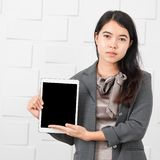 Aziatische dame in toevallige zaken, tablet ter beschikking stock afbeelding