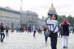 Aziatische de verschijningsfoto's van de mensentoerist op cameraaantrekkelijkheden op het Paleisvierkant van St. Petersburg, Rusl royalty-vrije stock foto
