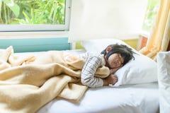 Aziatische die meisjesslaap op bed met deken wordt behandeld Stock Afbeelding