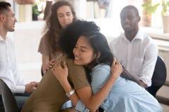 Aziatische en Afrikaanse vrouwen die gevend psychologische steun tijdens therapie omhelzen royalty-vrije stock foto