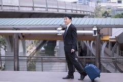 Aziatische en gelukkige Zakenman die, dragend kostuum met bagage glimlacht, royalty-vrije stock fotografie