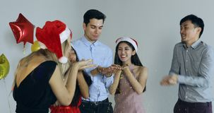 Aziatische en Kaukasische blazende confettien samen stock videobeelden