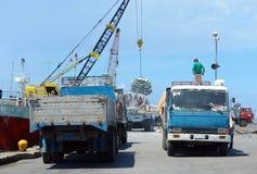 Aziatische exotische havenactiviteit met vrachtwagens en schip. stock foto's