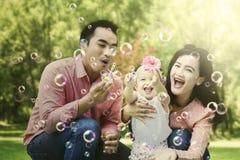 Aziatische familie blazende bellen op het park stock foto's