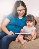 Aziatische familie die een tabletcomputer, het concept van de huisschool houden Stock Fotografie