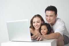 Aziatische Familie die Laptop met behulp van Royalty-vrije Stock Foto
