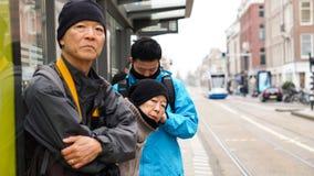Aziatische familie die op bus bij bushalte in de reisreis van Europa wachten Royalty-vrije Stock Foto's