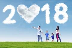 Aziatische familie die op wolken richten Stock Afbeeldingen
