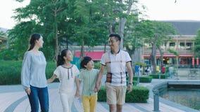 Aziatische familie die samen op opgewekte promenade lopen, wanneer het bekijken elkaar Stock Foto's