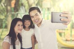 Aziatische familie die selfie bij het park nemen Royalty-vrije Stock Afbeeldingen