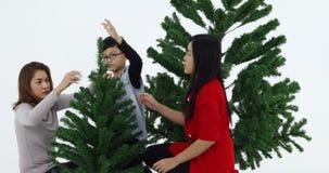 Aziatische familie gemaakt tot takken van Kerstboom stock videobeelden