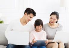 Aziatische familie met laptop op bank stock foto's