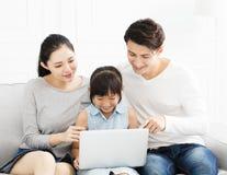 Aziatische familie met laptop op bank stock afbeeldingen