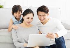 Aziatische familie met laptop op bank royalty-vrije stock foto