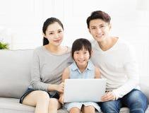 Aziatische familie met laptop op bank Royalty-vrije Stock Fotografie