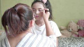 Aziatische familie met moeder die make-up doen aan haar meisje in de ruimte stock footage