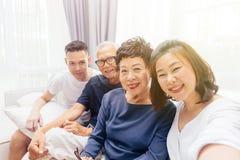 Aziatische familie met volwassen kinderen en hogere ouders die selfie en op een bank thuis zitten nemen Gelukkige en ontspannende royalty-vrije stock afbeelding