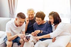 Aziatische familie met volwassen kinderen en hogere ouders gebruikend een mobiele telefoon en thuis samen ontspannend op een bank stock foto