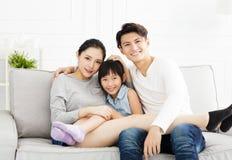 Aziatische familie op bank in woonkamer stock fotografie