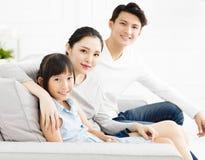 Aziatische familie op bank in woonkamer stock afbeeldingen