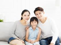 Aziatische familie op bank in woonkamer royalty-vrije stock afbeelding