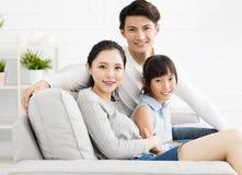 Aziatische familie op bank in woonkamer stock afbeelding