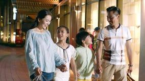 Aziatische familie van 4 die & buiten een winkelcomplex bij nacht in langzame motie lopen winkelen stock videobeelden
