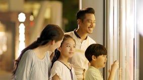 Aziatische familie van 4 die & winkelvenster in langzame motie bevinden zich onderzoeken stock video
