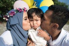 Aziatische familiemoeder en vader die hun zoon kussen stock fotografie