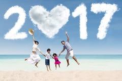 Aziatische familiesprong op strand met 2017 Royalty-vrije Stock Afbeeldingen