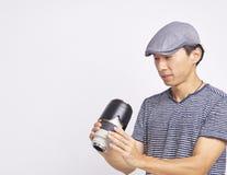 Aziatische fotograaf die geïsoleerde lens controleren op wit Stock Afbeelding
