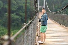 Aziatische fotograafmens in jeansjasje die zich op erfenis houten brug bevinden met exemplaarruimte royalty-vrije stock foto's