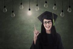 Aziatische gediplomeerde onder gloeilampen in klaslokaal Royalty-vrije Stock Fotografie