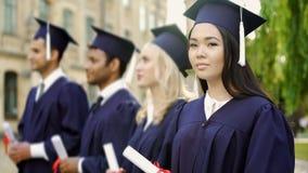 Aziatische gediplomeerde student met diploma, die in camera, internationale studies glimlachen royalty-vrije stock fotografie