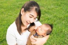 Aziatische 2 gelukkige babymaanden van het gevoel en glimlachen met haar binnen moeder Stock Afbeeldingen