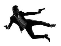 Aziatische gewapende manmoordenaar die schietend silhouet springt Stock Foto