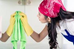 Aziatische gezinshulp die het huis met doek schoonmaken stock afbeelding