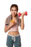 Aziatische gezonde trainingmeisje het drinken jus d'orangelift dumbbel Stock Fotografie