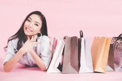 Aziatische glimlachende vrouw zo gelukkig met haar die in toevallige kleding met het winkelen zakken op de muur roze achtergrond  stock afbeeldingen