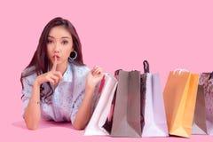Aziatische glimlachende vrouw zo gelukkig met haar die in toevallige kleding met het winkelen zakken op de muur roze achtergrond  stock afbeelding