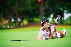 Aziatische golfspeler die op het groene gras leggen Stock Afbeeldingen