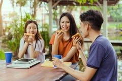 Aziatische groep die samen pizza in het breken van tijd eten royalty-vrije stock afbeeldingen