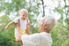 Aziatische grootvader dragende kleinzoon Stock Foto's